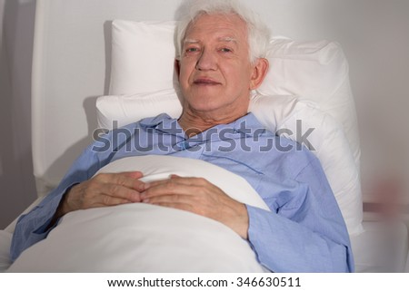 Seriously ill elderly patient lying in hospital bed - stock photo