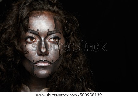 seriuos metal body art face of women isolated on black
