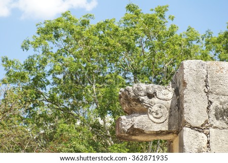 Serpent head decoration on the Mayan ball court in Chichen Itza, with green vegetation in the background - stock photo