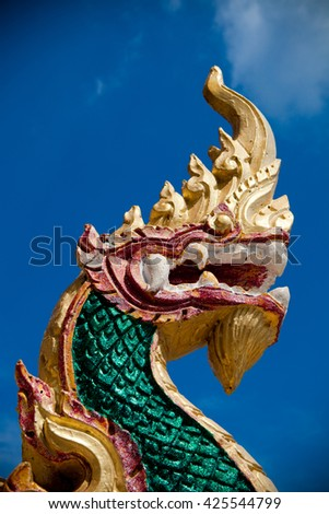 Serpent stucco with blue clear sky at Chalong Temple, Phuket southern of Thailand. - stock photo
