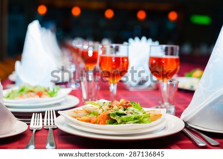 Served banquet table with glasses and salads. - stock photo