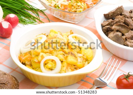 Served bowl of braised potatoes on a table
