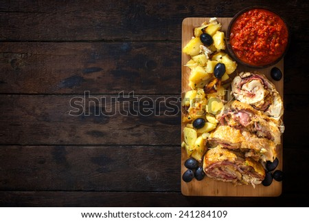 Served chicken roll with baked potatoes and ajvar salad on wooden background with blank space - stock photo