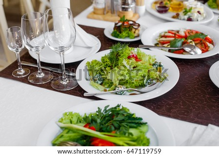 Served dishes to the table for holiday. Cutlery and food on white tablecloths in the restaurant. Design a festive Banquet. Luxurious food for guests and visitors.
