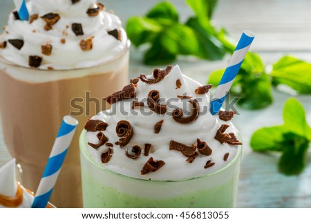 Served drink with mint as the main ingredient mixed with ice cream and milk. Leaves of mint and chocolate milkshake in the blurred background. Chocolate chips for brighter taste. - stock photo