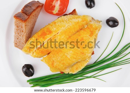 served fish fillet with greek olives,tomatoes,chives and lemon over white plate - stock photo