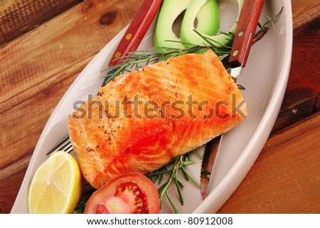 served fish: roast salmon fish over glass plate over wood - stock photo