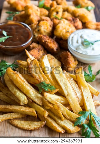 Served french fries and chicken nuggets in background on wooden board,selective focus - stock photo