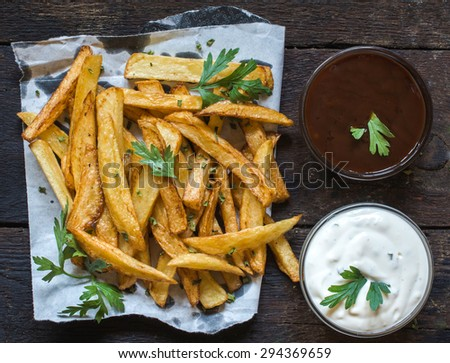 Served french fries and sauces on wooden background,from above  - stock photo