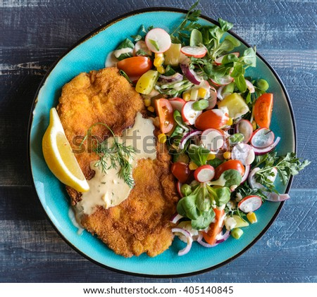 Served fried catfish fillet and salad in the plate