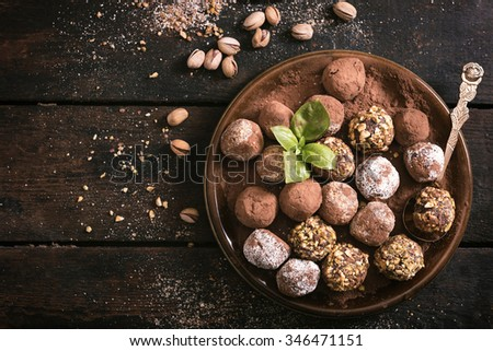 Served homemade chocolate pralines in the plate on wooden background  - stock photo