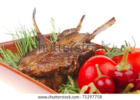 served main course: boned roasted ribs served with raw cherry tomatoes and fresh vegetables - stock photo