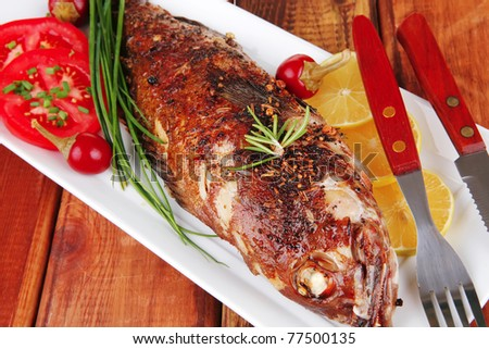served main course on wood: whole fried seabass on plate with lemons,tomatoes and peppers - stock photo