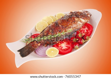 served main course: whole fried seabass served on plate with lemons,tomatoes and peppers - stock photo