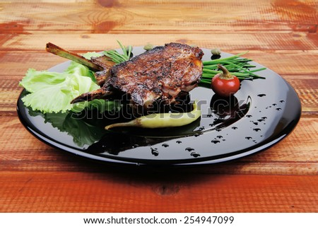 served meat: spiced barbecued ribs on black plate with vegetables - stock photo