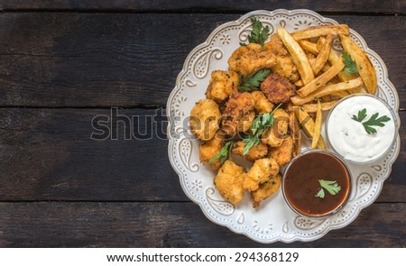 Served plate with fried chicken nuggets and french fries,blank space on the left side - stock photo