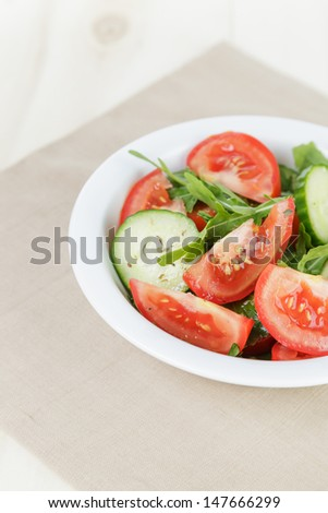 served plate with mix salad from tomatoes and cucumbers on table