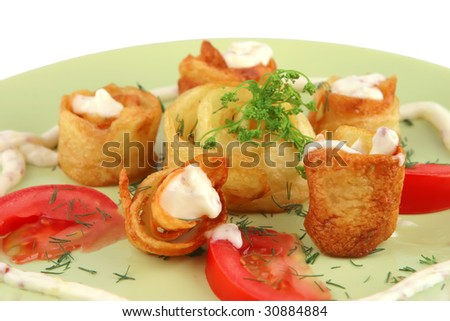 served potatoes with sauce on light dish - stock photo