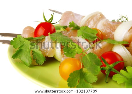 served raw chicken kebabs on dark plate