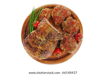 served roast meat on wooden plate with tomatoes - stock photo