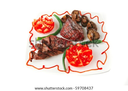 served roast veal fillet on a white plate with tomatoes - stock photo
