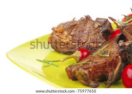 served savory plate: meat ribs with chives and red hot peppers on green - stock photo