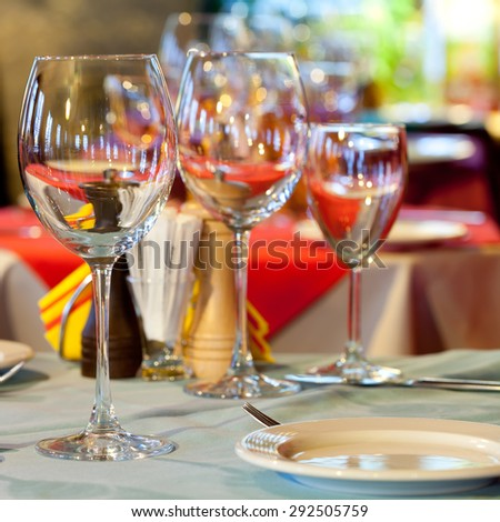 Served table. Empty wine glasses, white plate and cutlery. closeup. Bright blurred and soft restaurant, romantic cafe interior background. dining time. side view. soft focus.