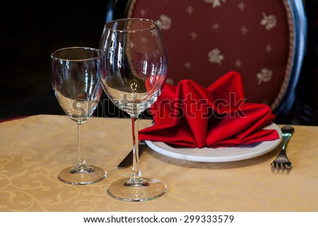 Served table in a restaurant. Yellow tablecloth, red napkins, serving white plate and glassware. Wine glasses and cutlery. old chair background. - stock photo