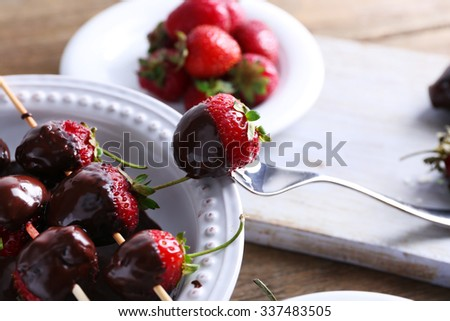 Served table with delicious strawberries in chocolate on wooden background - stock photo