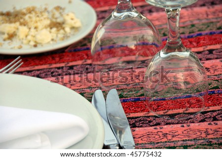 served table with plates, silverware and turned wineglasses