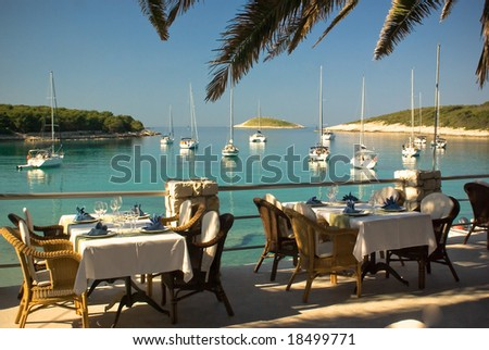 Served tables at yachting club beach restaurant - stock photo