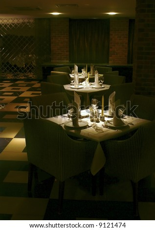 Served tables in restaurant interior on dark background - stock photo