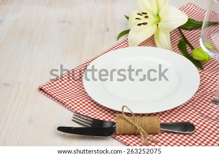 Served wooden restaurant table with settings on red checkered tablecloth - stock photo