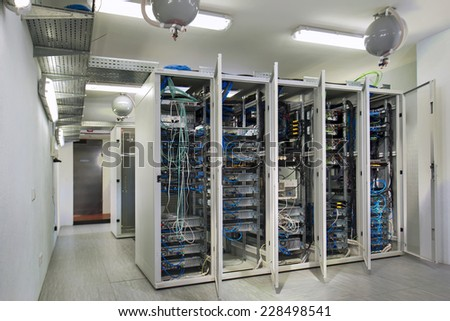 server room with open doors of cabinets for servers - stock photo