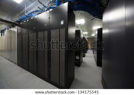 Server room with the telecommunication racks and lots of blue and black cables. - stock photo