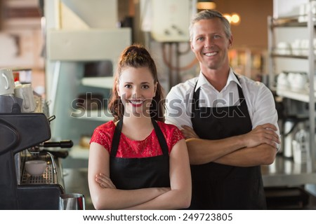 Servers smiling at the camera at the cafe - stock photo