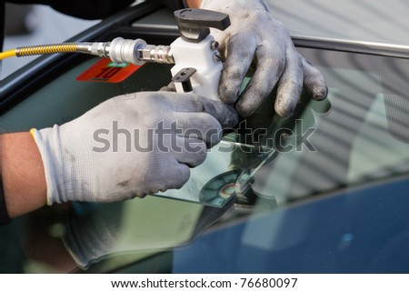 service agent  repairs dangerous crack in windhield on location without replacement glass for free - stock photo