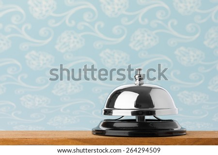 Service bell on wood board with blue background. - stock photo