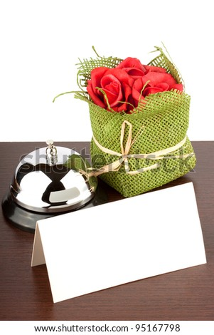 Service Bell with Blank Sign and red roses at Hotel Desk - stock photo