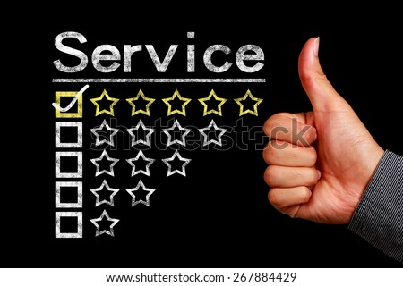 Service concept is on the blackboard with thumb up hand aside. - stock photo