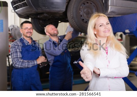 Service crew and happy driver standing near car and smiling indoor. Focus on woman - stock photo