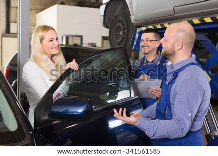 Service crew and satisfied woman driver standing near car and smiling. Focus on woman