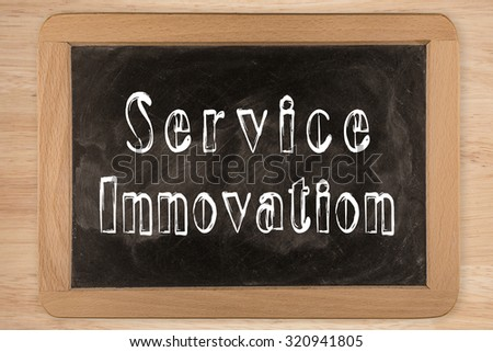Service Innovation -  chalkboard with  outlined text - on wood - stock photo
