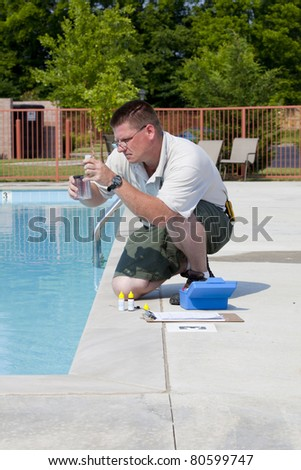 Service man checking chlorine, PH and other chemical levels in community pool - stock photo