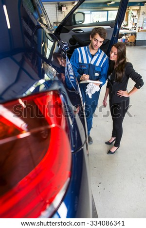 Service mechanic showing a customer the bill of materials and work, don in servicing and repairing her car - stock photo