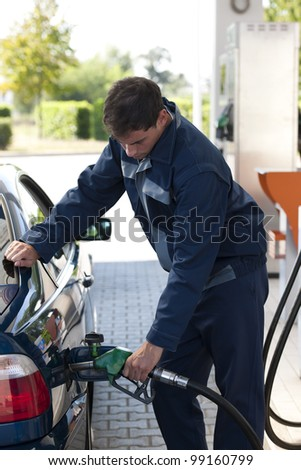 Service station worker filling up car with fuel - stock photo