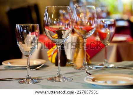 Service: table in a restaurant with a tablecloth, napkins, wine glasses and cutlery. - stock photo