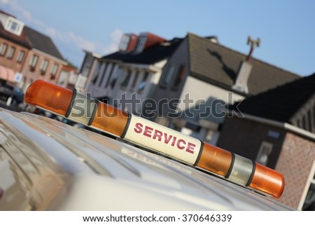 service vehicle with yellow beacon lights in urban area - stock photo