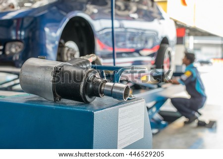 Serviceman checking suspension in a car at garage