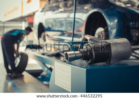 Serviceman checking suspension in a car at garage , process in vintage style